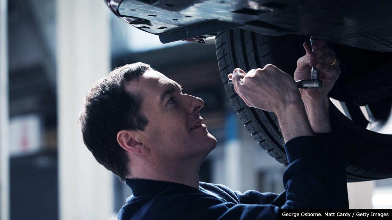 George Osborne as a mechanic working on a car